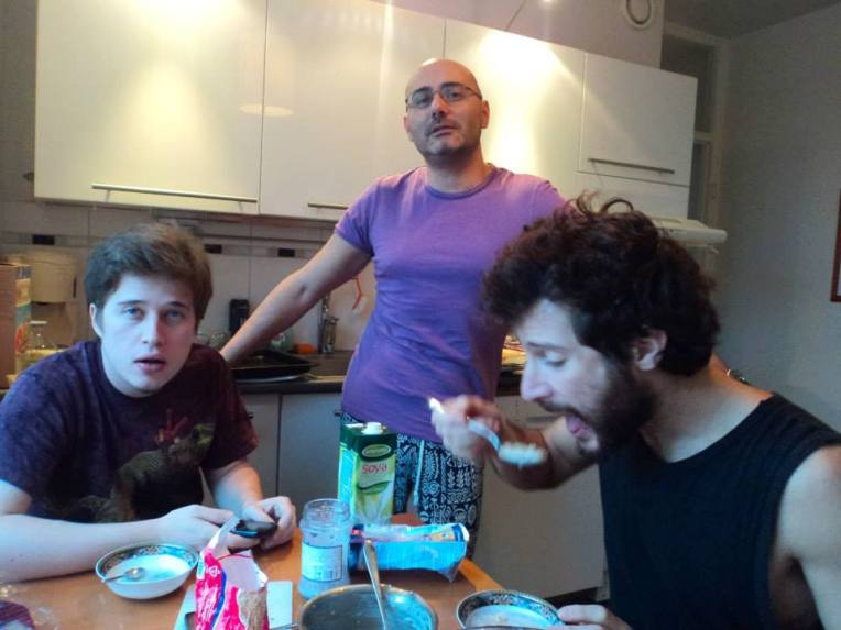 The creepy guy is eating while other couchsurfers are scared of him