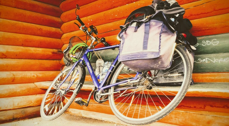 A bicycle hanging by it's right pedal on a wooden bench in a bus stop