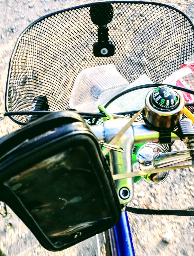 The handlebar of the bicycle with phone older, compass-bell and basket