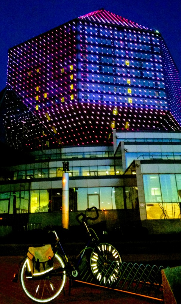 A bicycle parked in front of a diamond shaped, colorful, building in the night