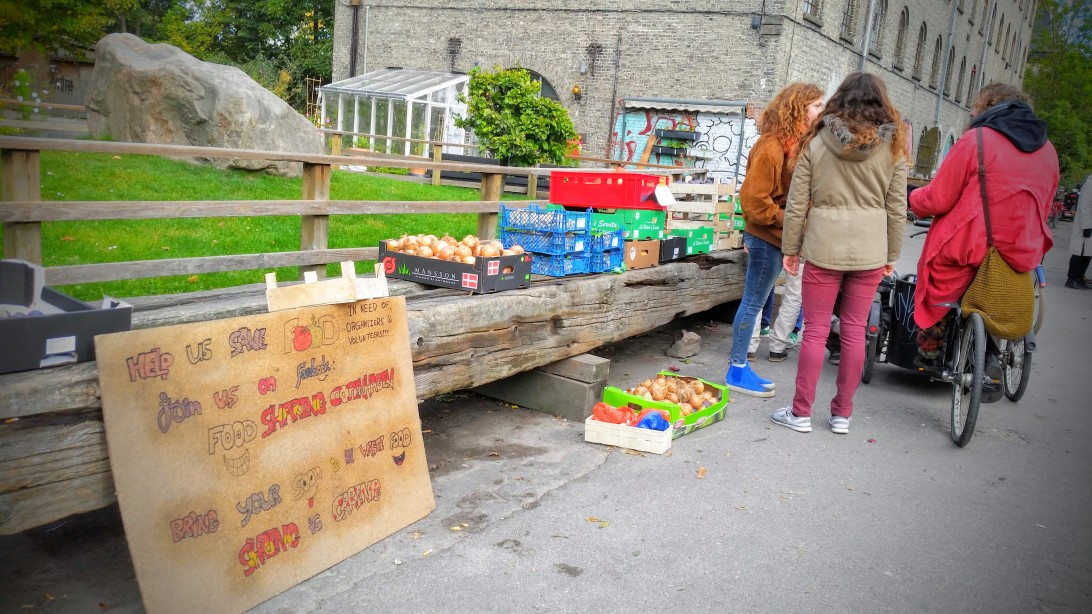 People standing in front of boxes full of vegetables.