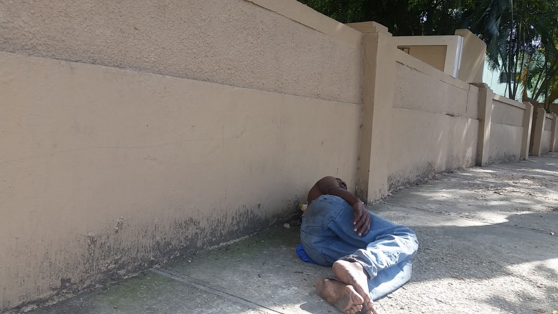 A man sleeping in the street with no shoes