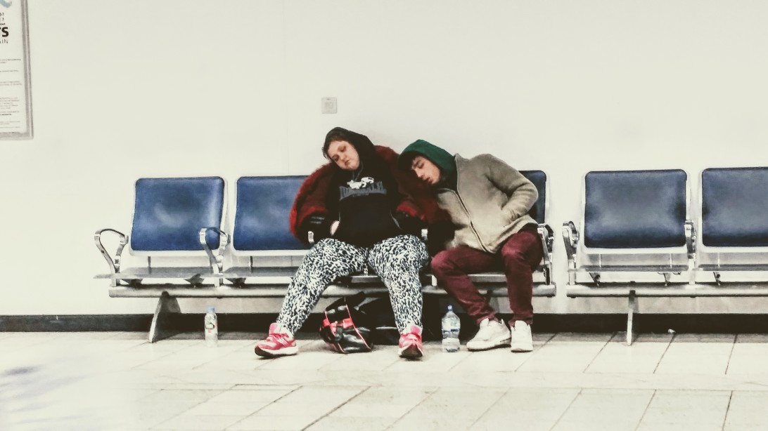 A woman and a boy sleeping on a the aligned chairs of an airport