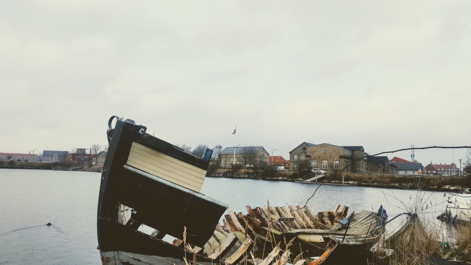 A totally broken small boat, black and white, behind which you can see some typical Danish style buildings in the outskirt of Copenhagen.