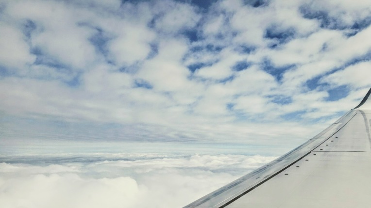 Front part of the right wing of a passenger airplane with clouds and blue sky
