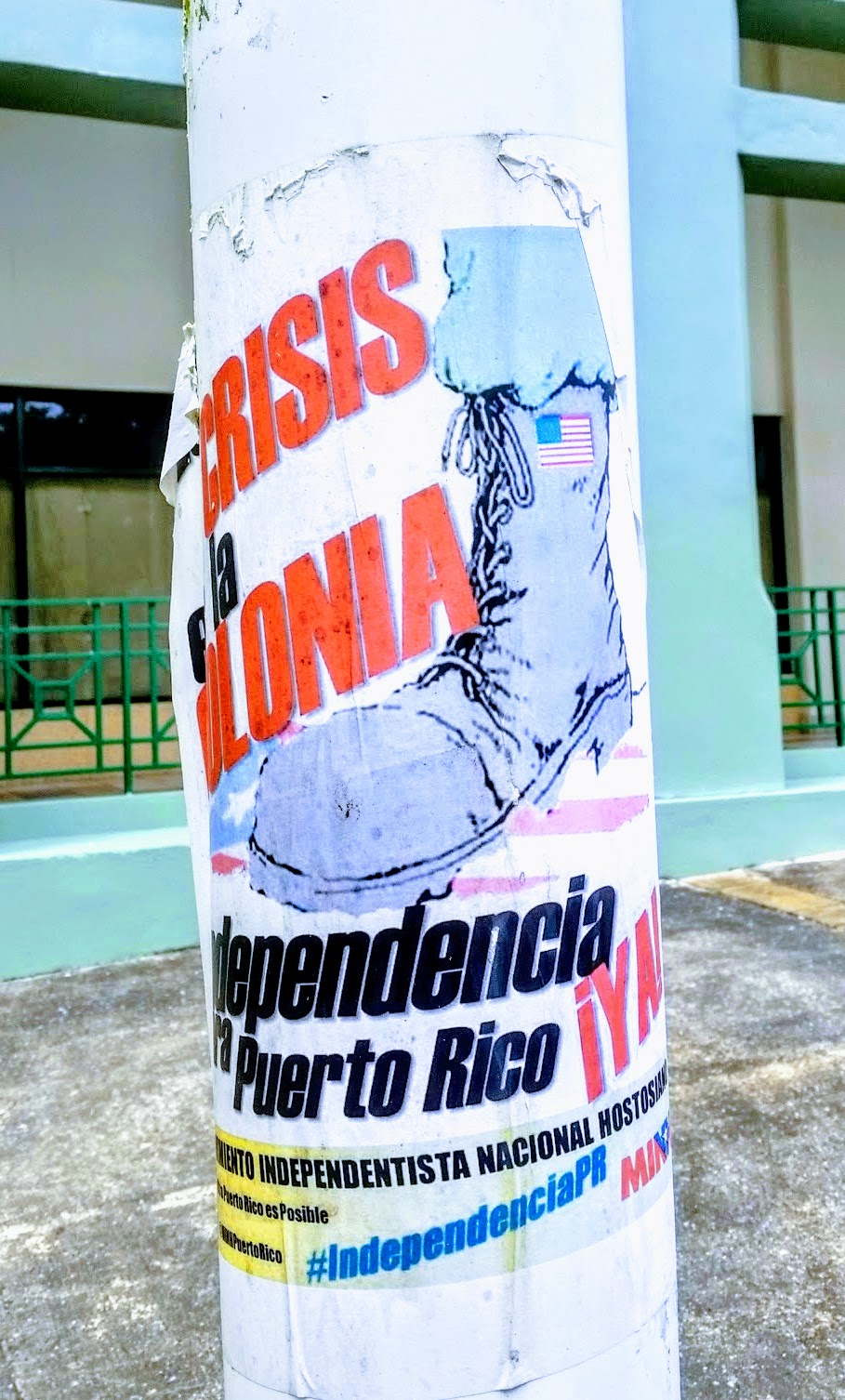 A poster on a light pole: a soldier shoe with the USA flag stepping on the PR flag