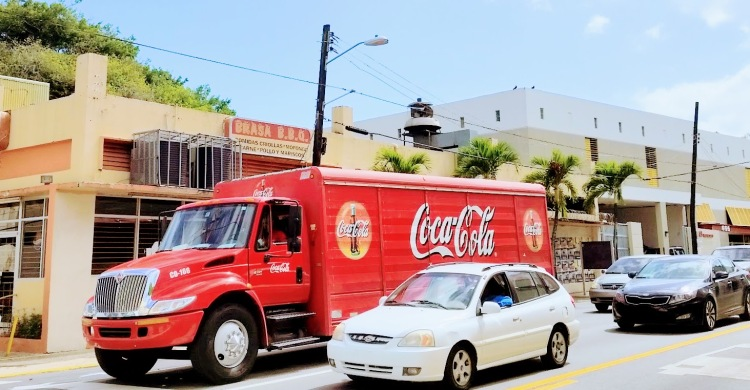 A red coca cola truck in street traffic