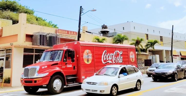 A red coca cola truck in street traffic