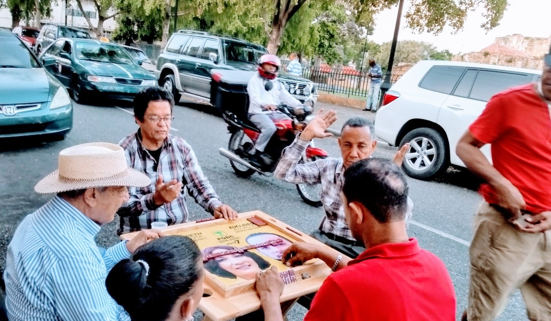 Five persons sitting on a square table playing domino,